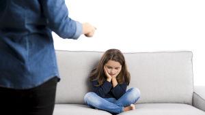En liten flicka får en utskällning av en vuxen man.