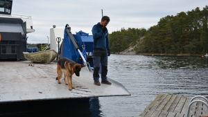 Man med hund står på fartygs landgång.