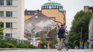 Gatuvy med en cyklist i förgrunden och en väggmålning i bakgrunden.