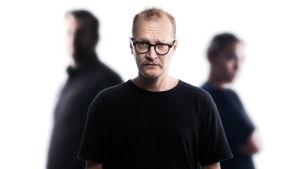 Janne Reinikainen katsoo etualalla kameraan, taka-alalla kaksi ihmishahmoa.