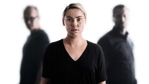 Sara Melleri katsoo etualalla kameraan, taka-alalla kaksi ihmishahmoa.