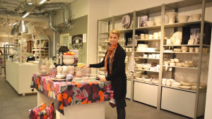 En kvinna står vid ett bord med kärl som är uppradade till försäljning. I bakgrunden syns flera kärl som också är till försäljning i Butiken. Kvinnan är Jeanina Enberg.