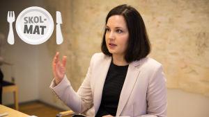 Undervisningsminister Sanni Grahn-Laasonen förklarar något och gestikulerar med handen. I det övre vänstra hörnet finns en stämpel med ordet Skolmat.