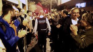 Folk applåderar när katalansk polis passerar vallokalen utan att ingripa.