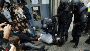 Kravallpolis håller nere två personer utanför en vallokal i Barcelona.