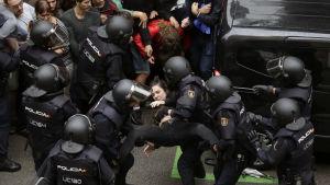 Spansk kravallpolis bär bort en ung kvinna.