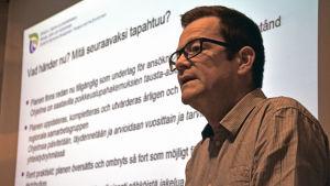Vincent Westberg framför en vit skärm med text på.