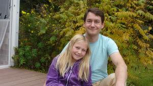 En pappa sitter med sitt barn framför en buske vars löv börjat gulna.