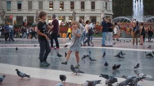 Barn och duvor på Plaza Cataluña.