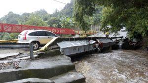 En bil kör över en bro som har skadats av storm och översvämning.