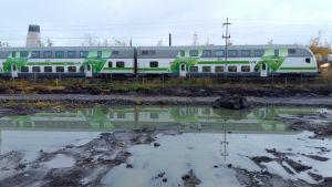VR:s grönvita tåg speglas i en vattensamling längs Kustbanan.