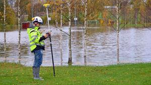 En lantmätare står vid en översvämmad bollplan.