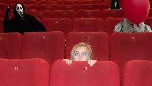 En ung kvinna kryper ihop bakom biografstolen, bakom henne syns olika monster från skräckfilmer.