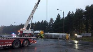En långtradares släp har vält på en asfaltväg. Lyftkranar och bärgningsbilar samt brandmän syns. Regnigt väder, skymning.