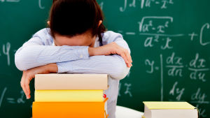 Trött skolelev böjd över sina skolböcker med svarta tavlan i bakgrunden.