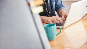En man som skriver på en laptop. Bredvid honom står en kaffekopp.