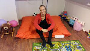 ung leende kvinna sitter på stor röd sittdyna omgiven av leksaker