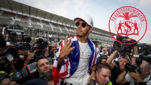 Lewis Hamilton omringad av kameramän.