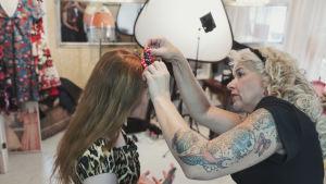 Anita Hallapelto knyter en rosett i programledaren Hannamari Hoikkalas hår.