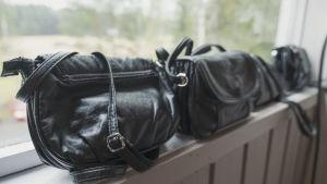 Tre svarta handväskor på rad på ett fönsterbräde.