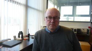 En man med glasögon sitter vid ett bord i ett kontor.
