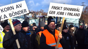 Bönder protesterar med plakat och traktorer i Vasa hamn.