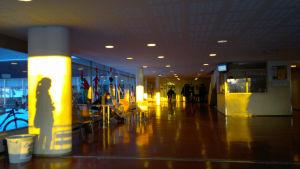Solen lyser lågt in i S:t Olofsskolans aula och skuggan av en elev syns på en pelare