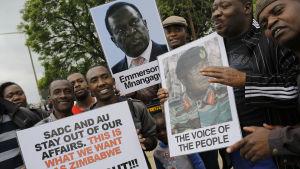 Flera av demonstranterna som deltog i lördagens massprotester hade med sig plakat till stöd för Emmerson Mnangagwa.