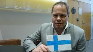 Rektor Mikael Bernas i Yttermark skola sitter med finska flaggan i handen.
