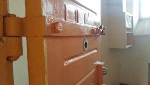 En orange dörr öppna still en fängelsecell i tidigare länsfängelset på Kakolabacken i Åbo.