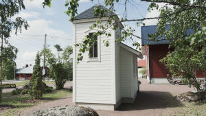 Hyvin pienen, valkoiseksi maalatun puukirkon pääty. Kirkko sijaitsee pihassa jossa useita punaisia rakennuksia.