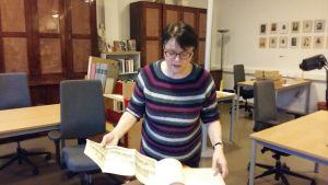 kvinna med kort mörkt hår och glasögon bläddrar i gammal bok