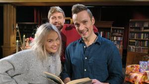 Tre personer poserar framför kameran med en bok.