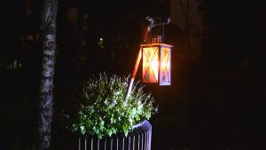 En lykta med ett ljus i hänger på en gren nerstucken i en blomkruka utomhus. Runt omkring är det mörkt.