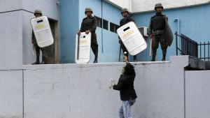 Demonstrant räcker ut en blomma åt säkerhetsstyrkor som står på en mur.