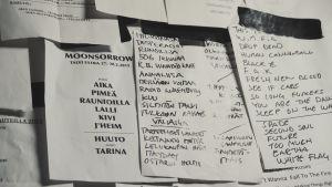Vita papper med låttitlar skrivna med svart tusch, upptejpade på vägg med svart isoleringstejp.