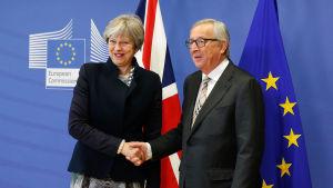 Theresa May och Jean-Claude Juncker skakar hand i Bryssel.