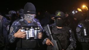 Poliser i Honduras står maskerade vid en polisstation.