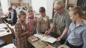 Läraren Päivi Hakoma visar gamla böcker för en grupp elever.
