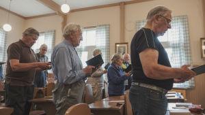 Vanhemmat herrasmiehet veisaavat vanhoista laulukirjoista pulpettien äärellä.