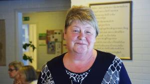 En kvinna ler på en bild, i bakgrunden syns en tavla och några personer i profil. Kvinnan heter Mona Andersson