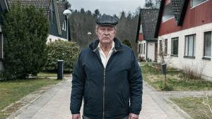 Rolf Lassgård poserar på gata i villaområde