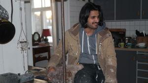 Ahmed Aljuaifari med en lurvig hund vid en gammal spis i familjen Hellgrens kök