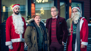 Reunoilla kaksi joulupukkia ja keskellä Kari Ketonen ja Antti Luusuaniemi.