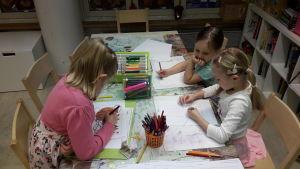 Tre flickor ritar på ett daghem.