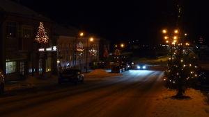 Julbelysning på en gata i Kristinestad. Ljusen till vänster i bilden och som är upphängda i stolpar föreställer julgranar, stjärnor och juleklockor.