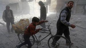 Invånare i Hamouria, östra Ghouta, tar sig fram i kvarter som nyss utsatts för en flygräd 3.12.2017.