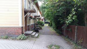 Blommor, gröna buskar och träd vid ingången till arbetarträhus en sensommardag.