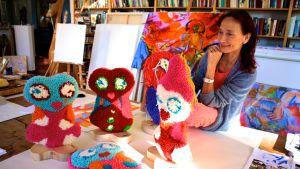 """Taiteilija Riitta Nelimarkka """"ateljeerissaan"""" Helsingin Marjaniemessä. Kuvassa näkyy villapystejä. Ne ovat hauskoja, värikkäitä olioita tai tyyppejä, joilla on erilaisia ilmeitä."""