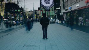 En mörkklädd man står med ryggen till och huva på huvudet still i stadsvimlet som rör sig runt honom.